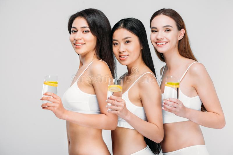 beautiful smiling multiethnic girls holding glasses with lemon water stock photography