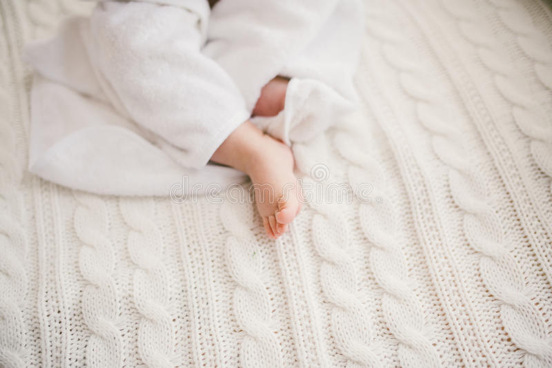 Beautiful smiling newborn baby boy covered with white bamboo towel with fun ears. Sitting on a white knit, wool plaid bright inter. Ior. The natural light from stock photography