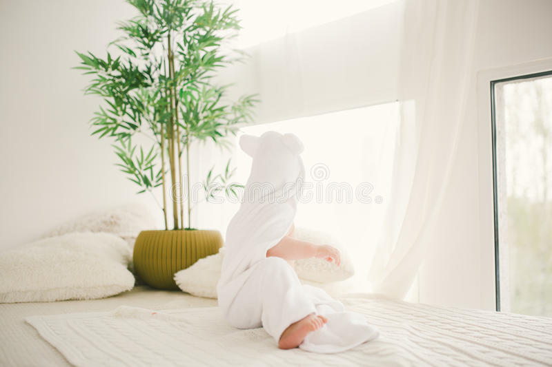 Beautiful smiling newborn baby boy covered with white bamboo towel with fun ears. Sitting on a white knit, wool plaid bright inter. Ior. The natural light from royalty free stock photo