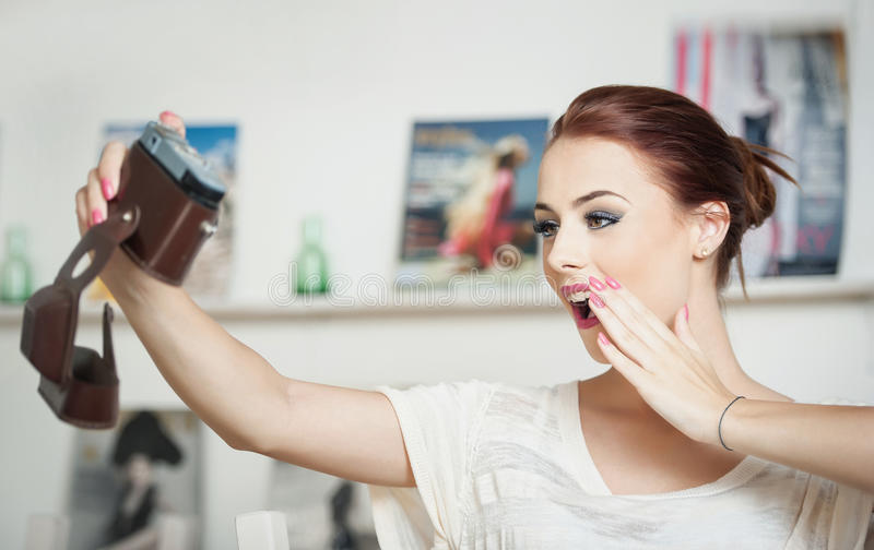 Beautiful, smiling red hair woman taking photos of herself with a camera. Fashionable attractive female taking a self portrait. Selfie, indoor, horizontal royalty free stock photo