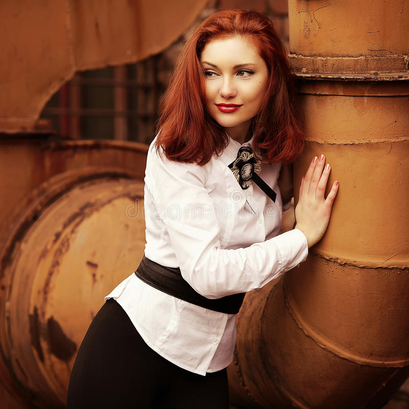 Beautiful smiling red-haired girl. In white blouse over background of rusty tubes. Retro (vintage) style. Outdoor shot royalty free stock photo