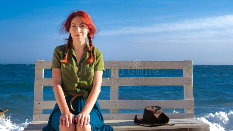 Beautiful smiling red-haired traveler girl sitting on a bench on the sea beach, dreams, relaxes and enjoys life. stock images