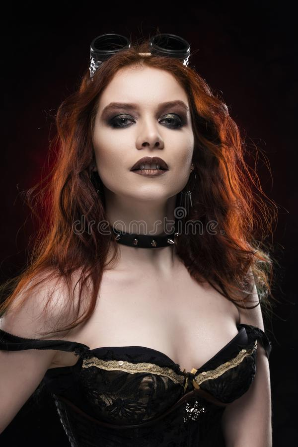 Beautiful smiling redhead cosplayer girl wearing a Victorian-style steampunk costume with a big breast in a deep neckline on red stock image