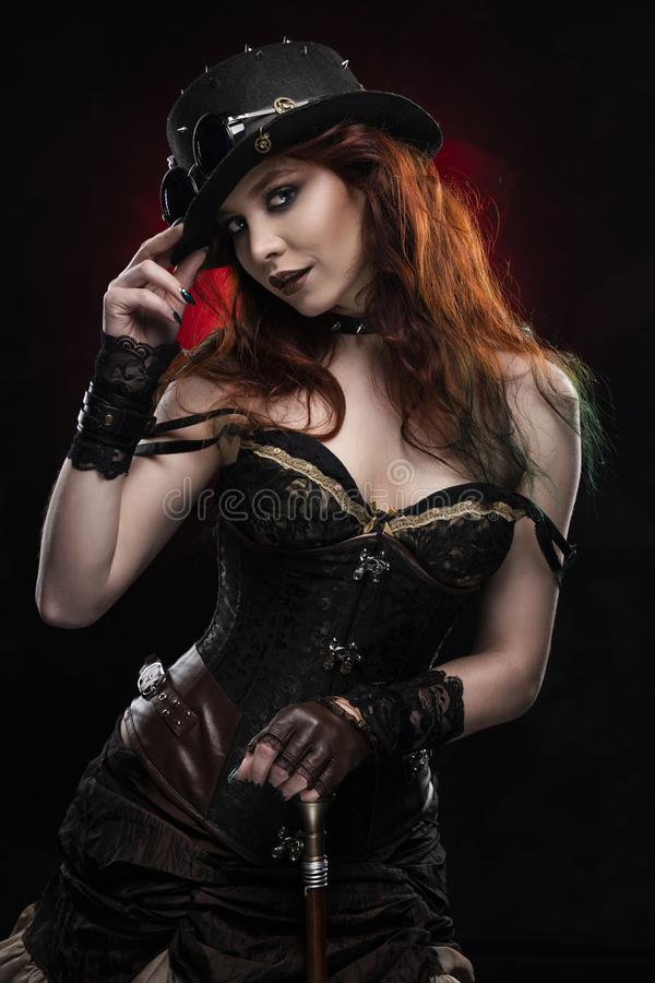 Beautiful smiling redhead cosplayer girl wearing a Victorian-style steampunk costume and hat with a big breast in a deep neckline. Rests on a cane. Red and stock photo