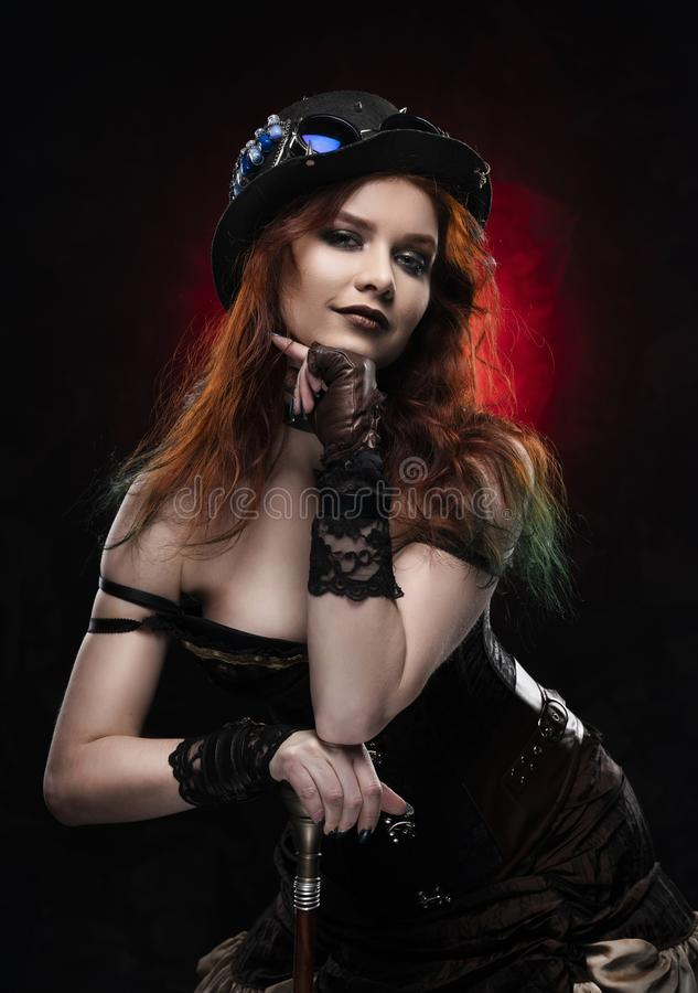 Beautiful smiling redhead cosplayer girl wearing a Victorian-style steampunk costume and hat with a big breast in a deep neckline. Rests on a cane. Red and stock image