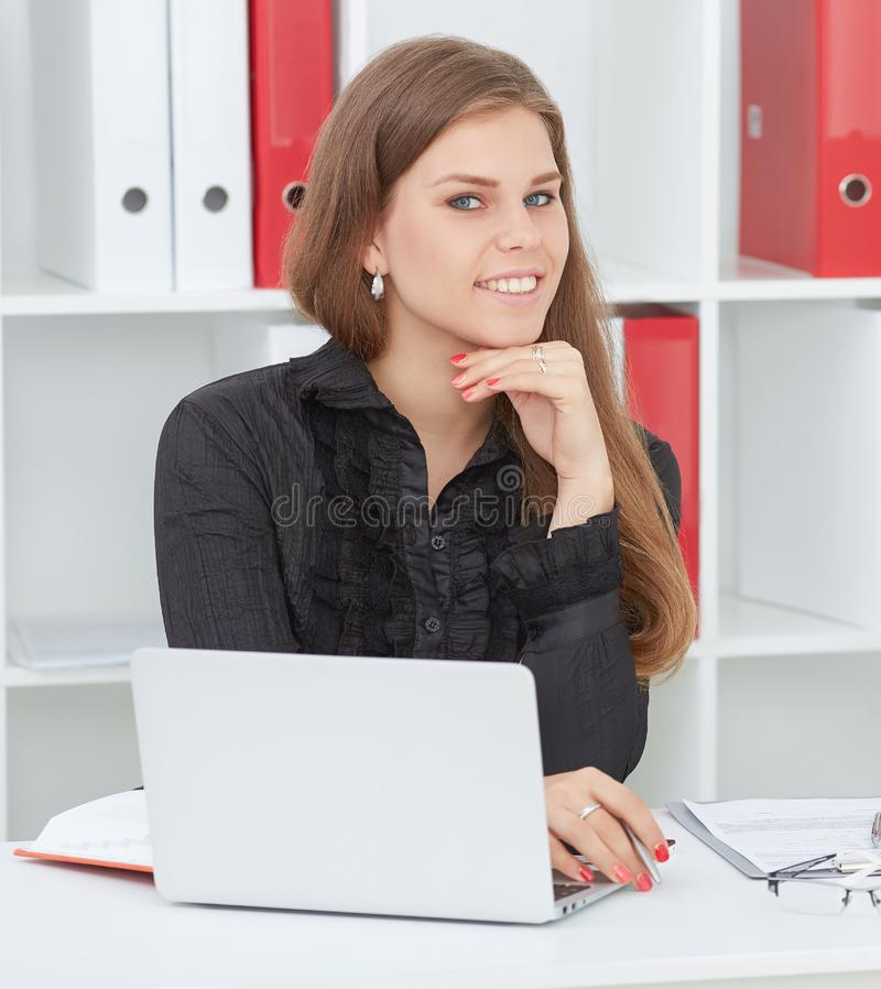 Beautiful smiling secretary sitting at the table with notebook looking at the camera. stock photos