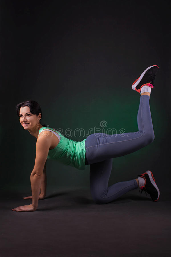 Beautiful smiling sporty woman doing exercise lifting legs on dark background with green backlight stock image