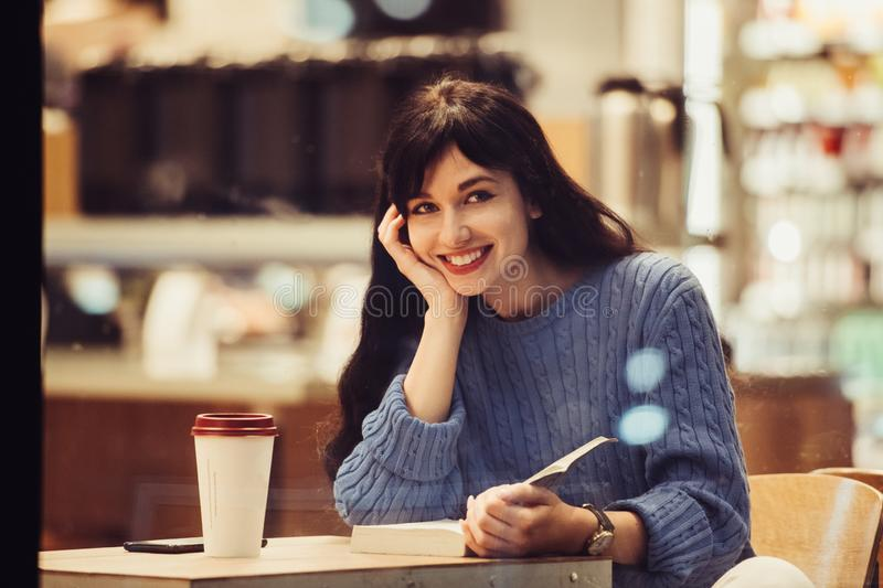 Beautiful smiling student woman reading a book in the cafe with warm cozy interior and drinking coffee stock image