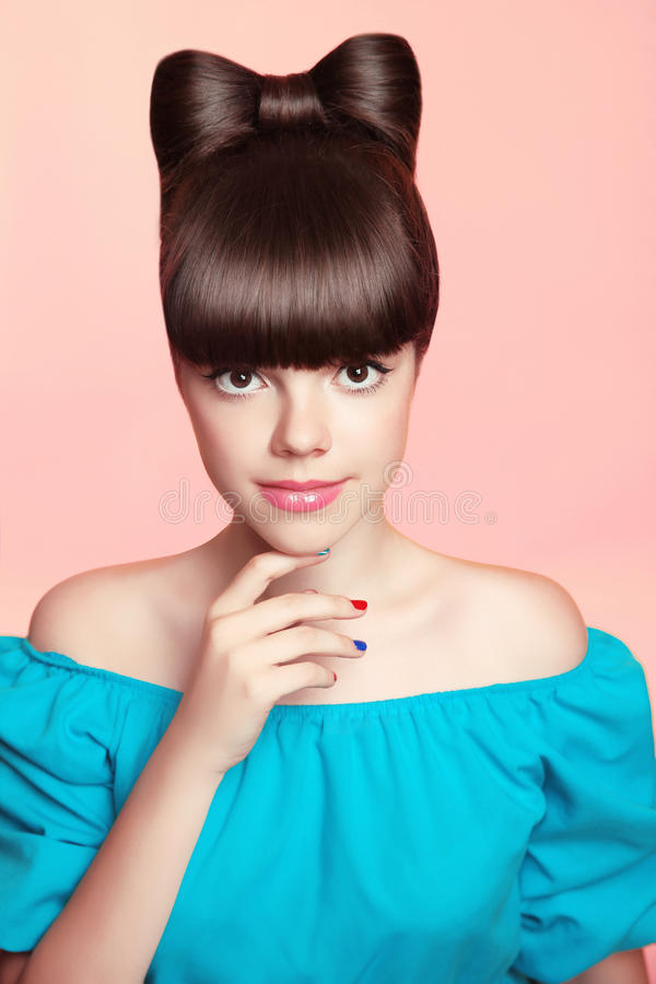 Beautiful smiling teen girl with bow hairstyle, makeup and colourful manicured polish nails. Funny brunette in blue dress isolate. D on studio pink background royalty free stock photography