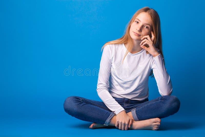 Beautiful stylish stylish teen girl on blue background. stock image