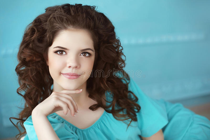 Beautiful smiling teen girl portrait, brunette with healthy curl. Y hair style in green dress lying over blue background stock photos