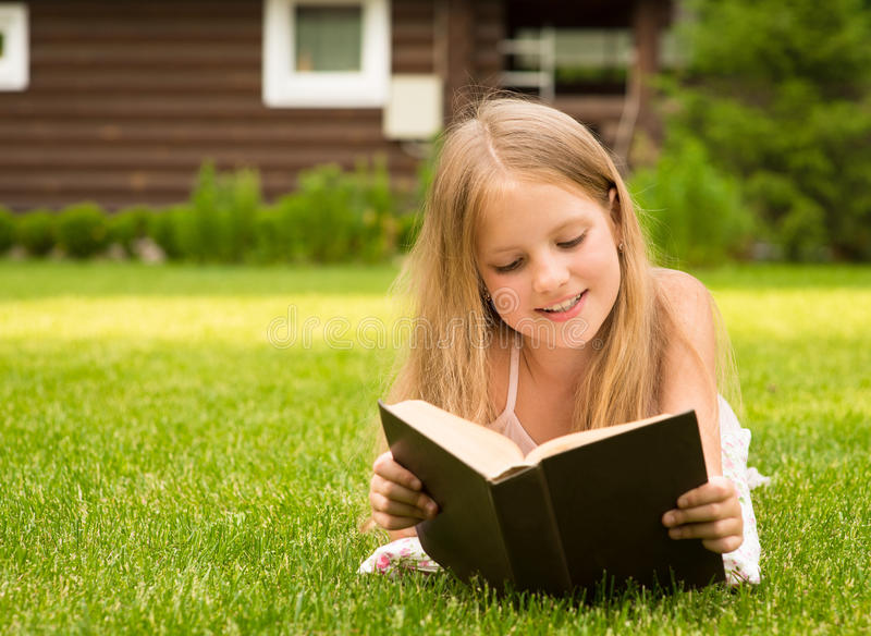 Beautiful smiling teenage girl lying on grass and read book royalty free stock images