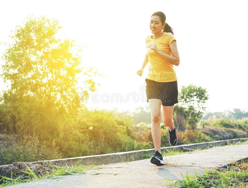 Beautiful smiling thai women is run and jogging  on the park trail. royalty free stock photos