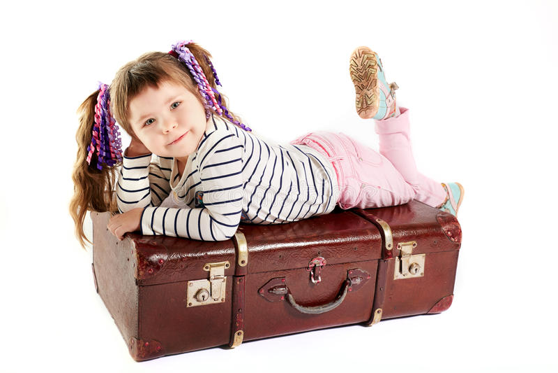Beautiful smiling toddler girl laying on retro suitcase. White background stock images