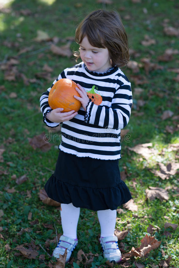 Beautiful smiling toddler girl wearing black and white Halloween outfit outdoors holding little pumpkin and smiling with royalty free stock photos