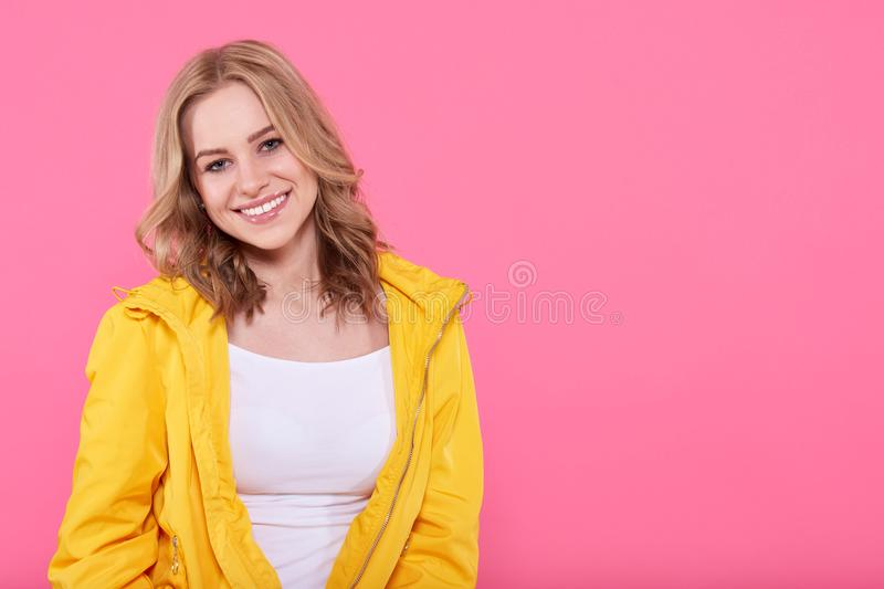 Beautiful smiling trendy teenage girl in bright yellow jacket looking at camera. Attractive young woman portrait over pastel pink. royalty free stock image