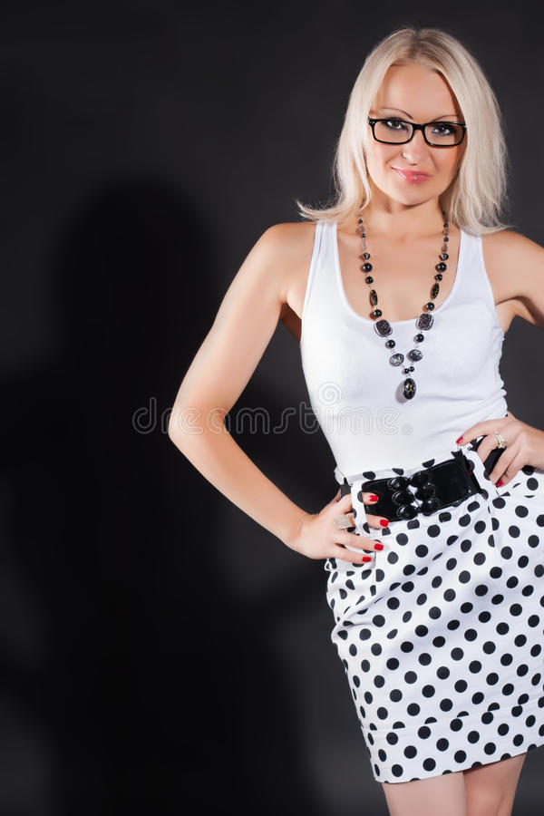 Beautiful smiling woman. Wearing glasses, throws a shadow on the background stock photo