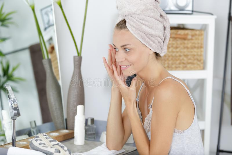 Beautiful smiling woman applying cream on face stock images