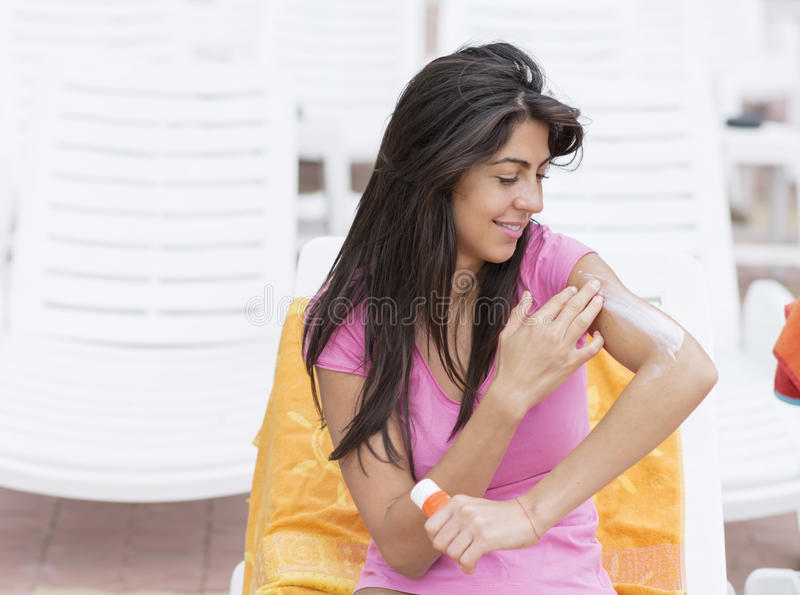Beautiful smiling woman applying sun-protection cream. Young woman smiling to camera, holding sun-protection cream stock image