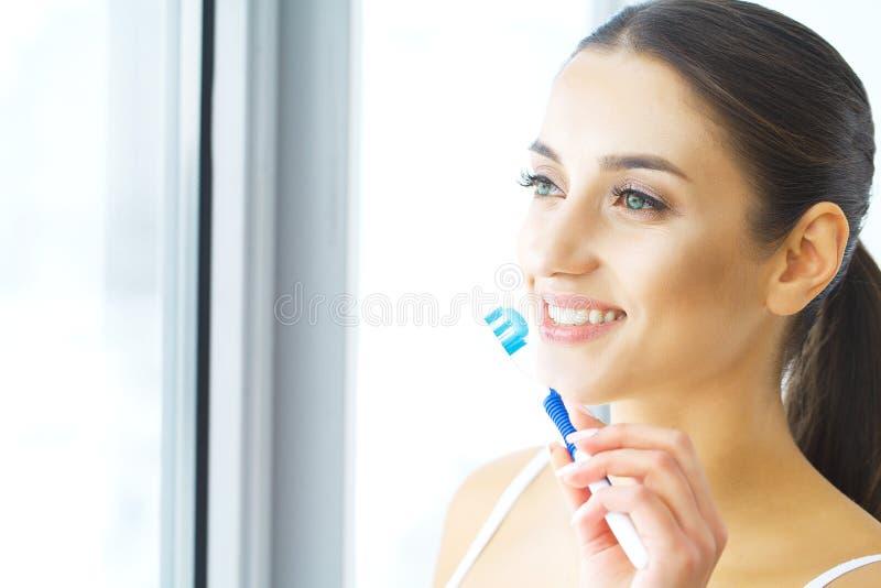 Beautiful Smiling Woman Brushing Healthy White Teeth With Brush. stock photo