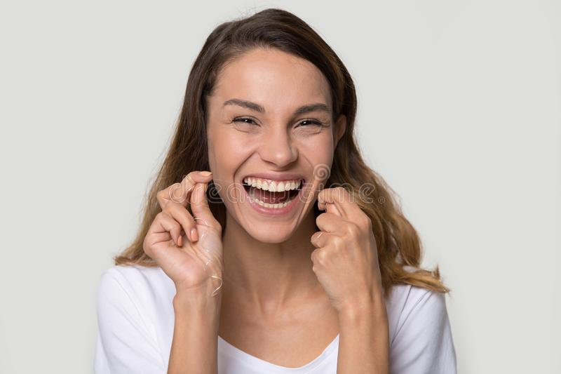 Portrait happy attractive woman cleaning teeth with dental floss. Beautiful smiling woman cleaning teeth with dental floss remove food between tooth preventing stock photography