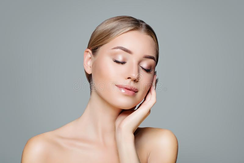 Beautiful smiling woman with clear skin relaxing. Facial treatment, haircare and cosmetology concept.  stock photos