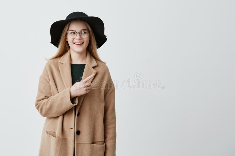 Beautiful smiling woman in coat over green sweater and eyeglasses pointing at blank white wall while demonstrating royalty free stock images
