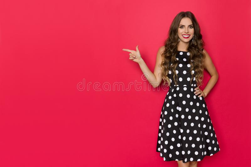 Beautiful Smiling Woman In Coctail Dress Is Pointing At Red Copy Space royalty free stock photo