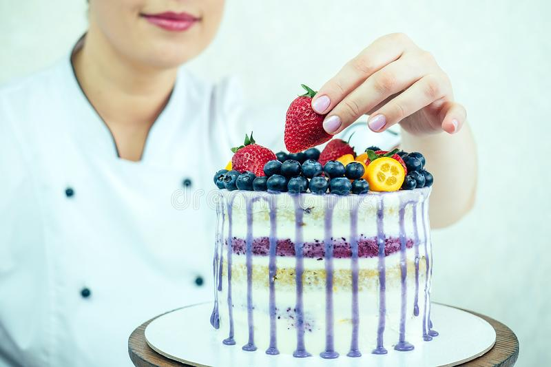 Beautiful and smiling woman confectioner in white work uniform adorns the cake in the kitchen. confectioner, cake stock photos