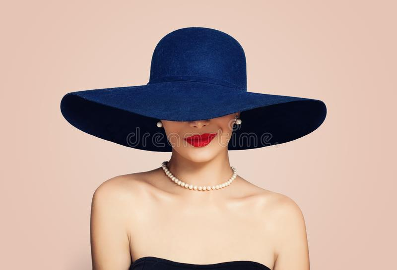 Beautiful smiling woman in elegant hat on pink background. Stylish girl with red lips makeup, fashion portrait royalty free stock photography