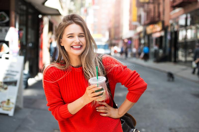 Beautiful smiling woman enjoy refreshment iced coffee drink on city street. stock photography