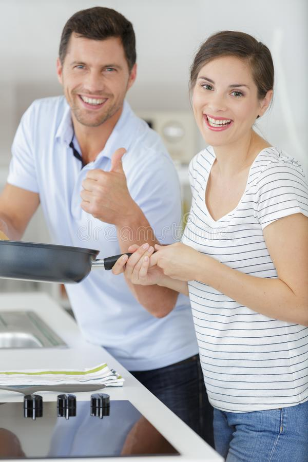 Beautiful smiling woman enjoying cooking with boyfriend stock images
