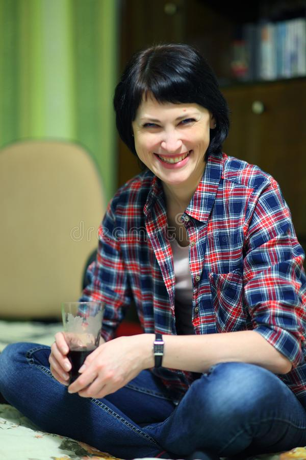 A beautiful smiling woman with a glass in her hand crosses her legs. royalty free stock photos