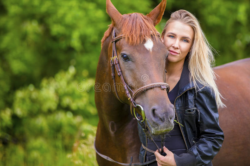 Beautiful smiling woman with her arabian horse in the field stock photography