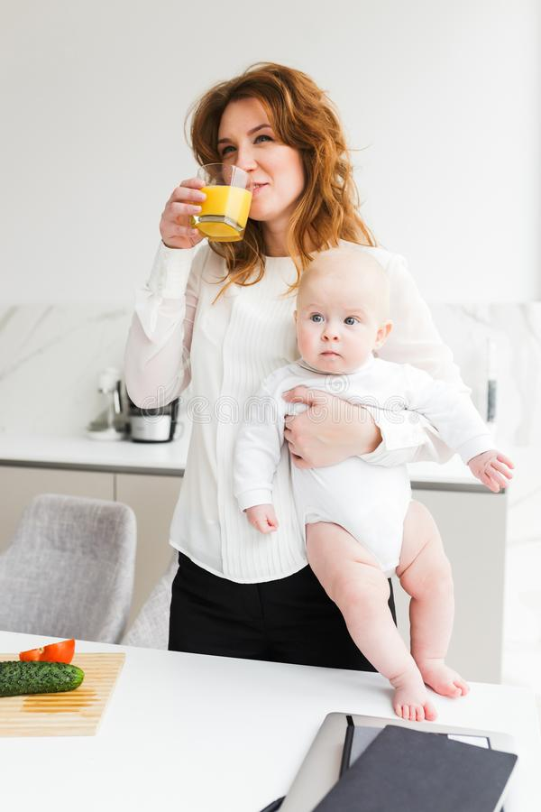 Beautiful smiling woman holding her cute little baby while drinking juice and cooking on kitchen royalty free stock image