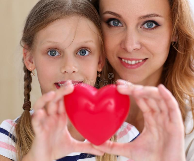 Beautiful smiling woman and kid hold red toy heart royalty free stock photo
