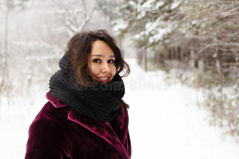Beautiful smiling woman with long brown hair in a coat from faux fur and big black scarf on a background of winter forest.  stock images