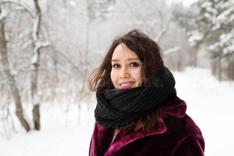 Beautiful smiling woman with long brown hair in a coat from faux fur and big black scarf on a background of winter forest.  royalty free stock photos