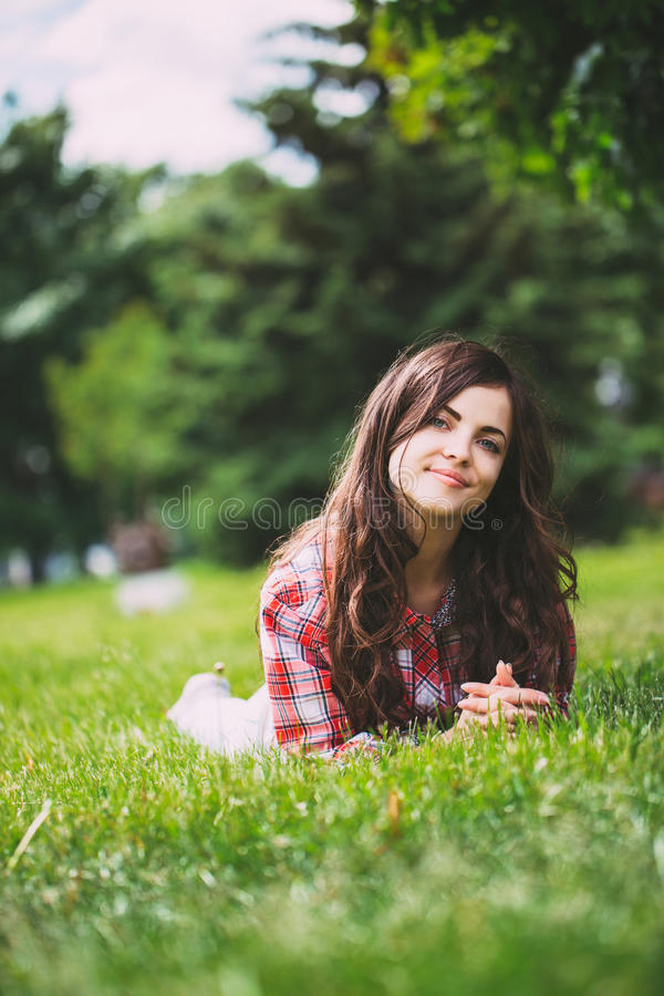 Beautiful smiling woman lying on a grass outdoor. royalty free stock photos