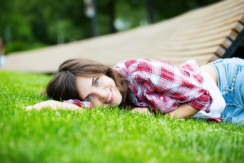 Beautiful smiling woman lying on green grass stock photos