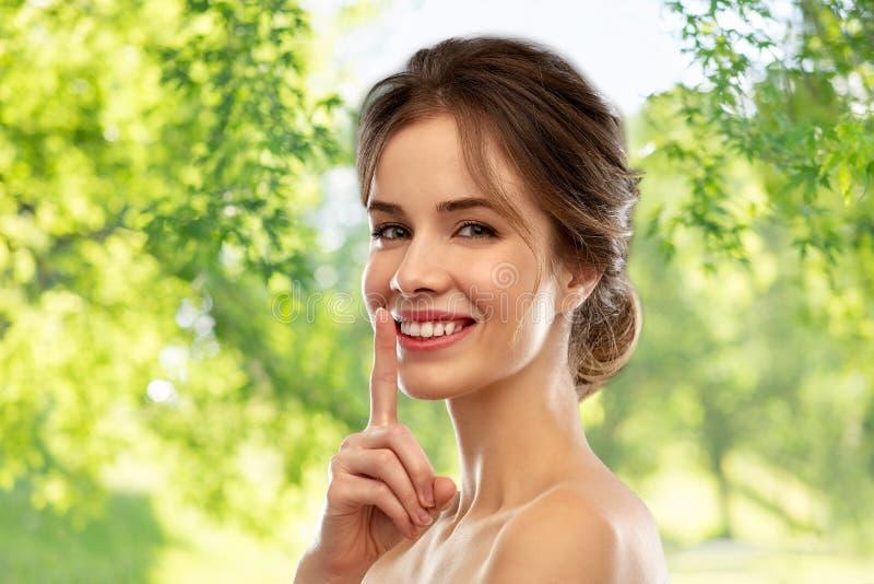 Beautiful smiling woman making hush gesture stock image