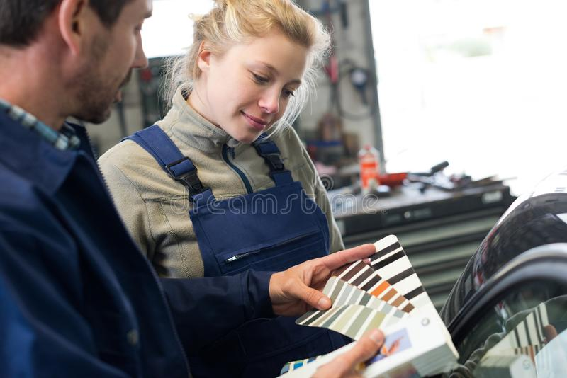Beautiful smiling woman mechanic in blue with mentor royalty free stock image