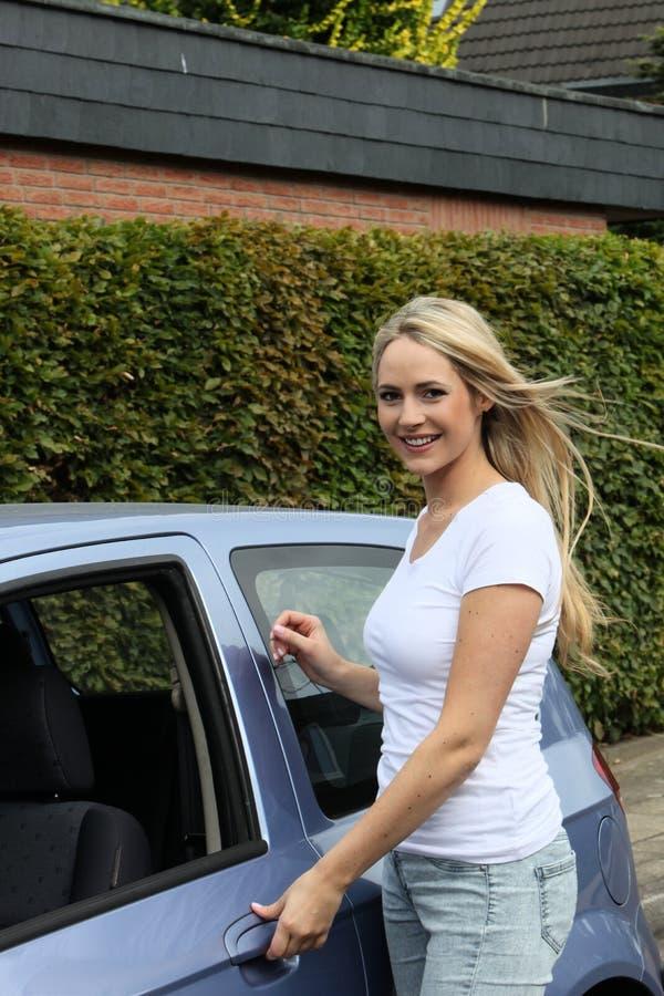 Beautiful smiling woman opening a car door stock photos