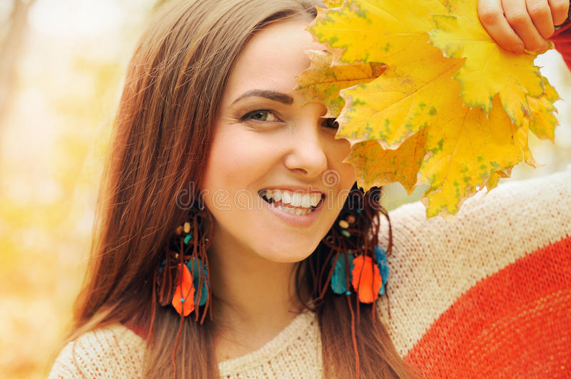 Beautiful smiling woman outdoor portrait, fresh skin and healthy smile, hold maple leaves bouqet front of face stock photo