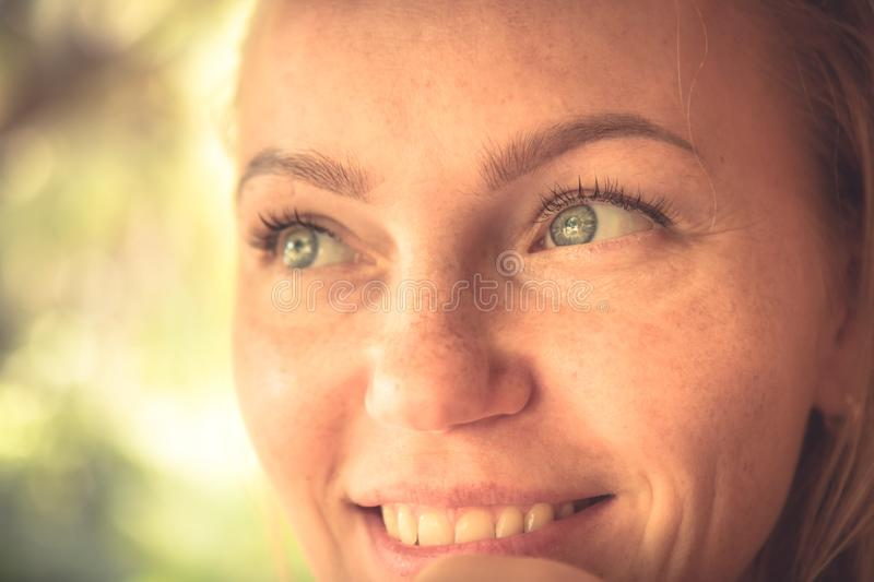 Beautiful smiling woman portrait in warm colors with sunlight on woman face with authentic smile and tan skin stock images