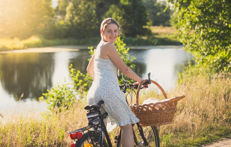 Beautiful smiling young woman posing on vintage bicycle in field at susnet royalty free stock photos