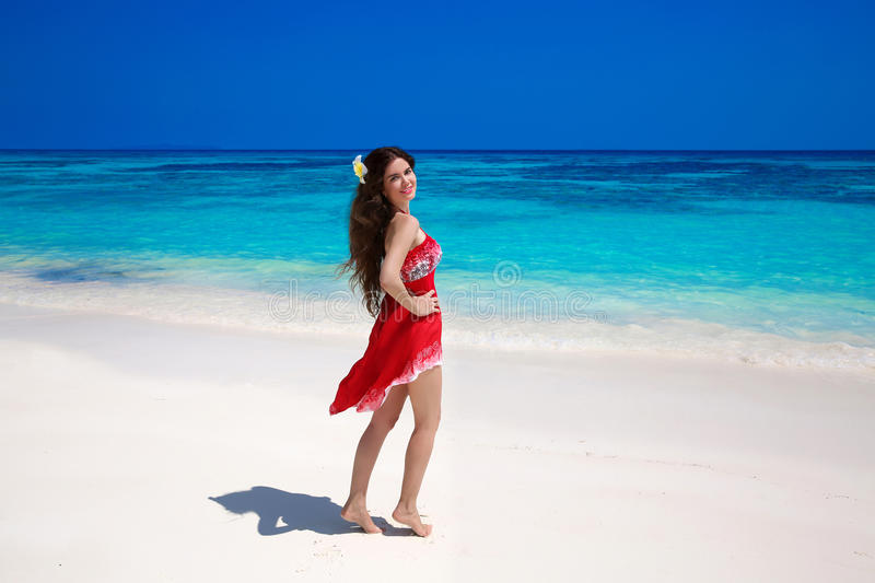 Beautiful smiling woman in red dress enjoying on exotic sea, tropical beach. summer outdoor portrait. Attractive girl model. Welln. Ess. Lifestyle. Bliss freedom stock photo