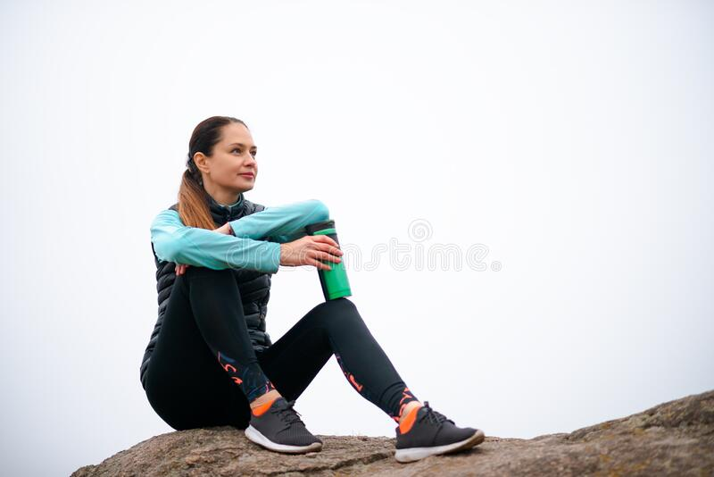 Beautiful Smiling Woman Resting after Running Outdoor. Workout at Autumn Evening. Sport and Healthy Active Lifesyle stock photo