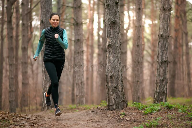 Beautiful Smiling Woman Running on the Forest Trail at Cold Autumn Evening. Sport and Active Lifestyle stock images