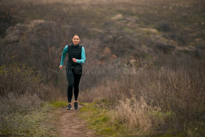 Beautiful Smiling Woman Running on the Mountain Trail at Cold Autumn Evening. Sport and Active Lifestyle stock image